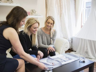 Bridal event planner with bride-to-be looking through dress catalog
