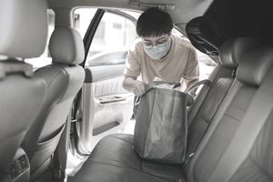 Masked Asian Woman Pulls Bag of Goods Out of Back Seat of a Car