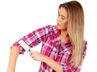 Woman in pink plaid shirt using a lint roller