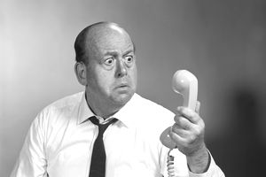 1960s MAN LOOKING SURPRIZED AT TELEPHONE WHEN HE FINDS HE IS NOT COVERED BY INSURANCE