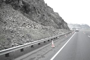 A highway with construction warning cones in mountainous terrine with rockfall protection system construction.