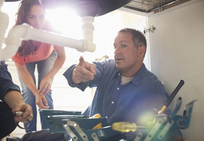 a handyman assessing a plumbing situation with a tenant