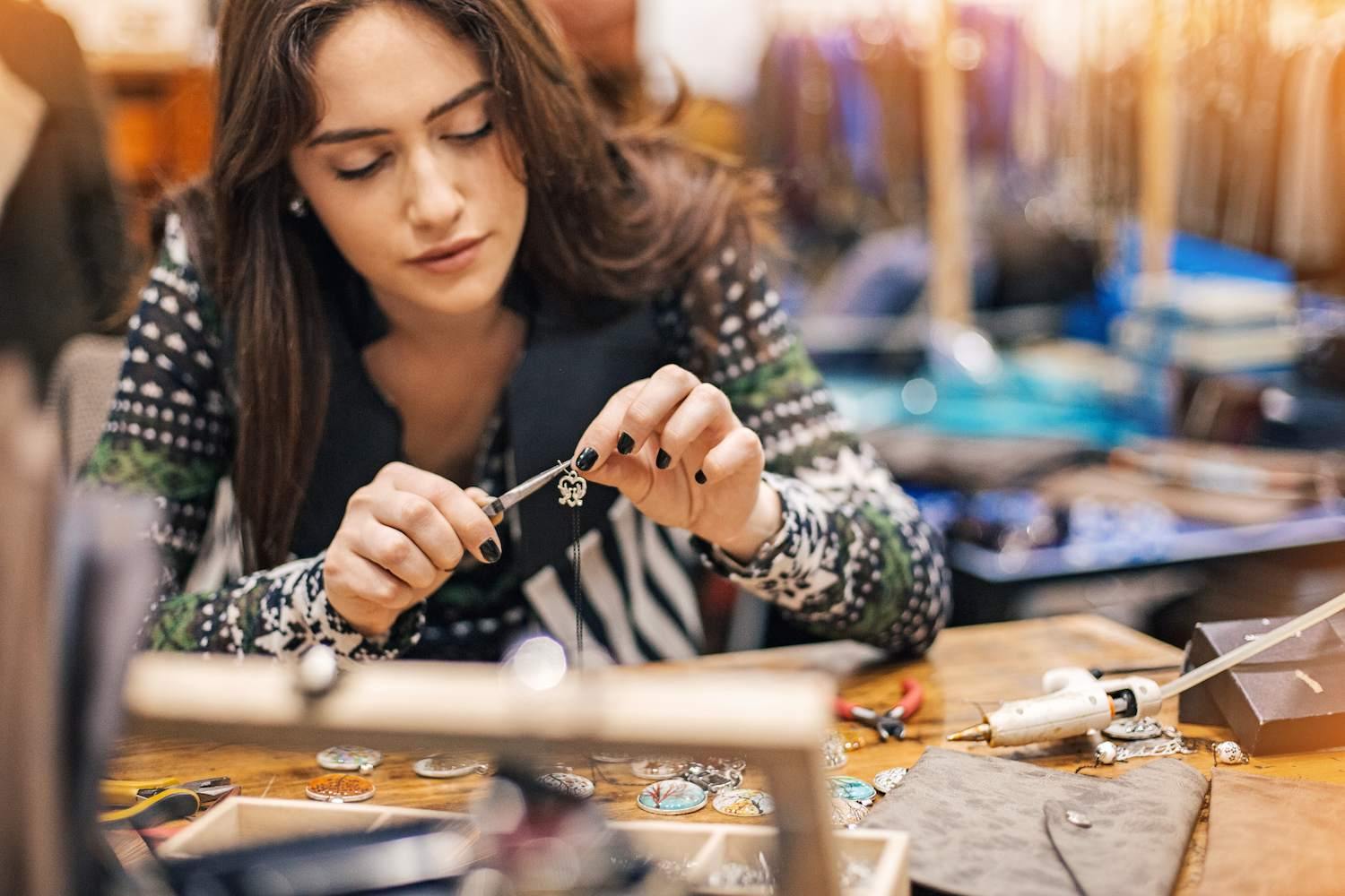 Jewelry designer working with metal and pliers in her studio