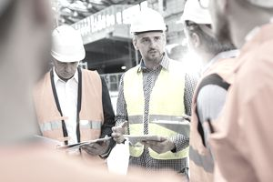 Male foreman, engineers and construction workers meeting at construction site