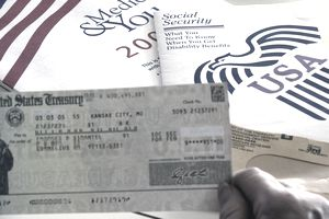 elderly person's hand holding social security check