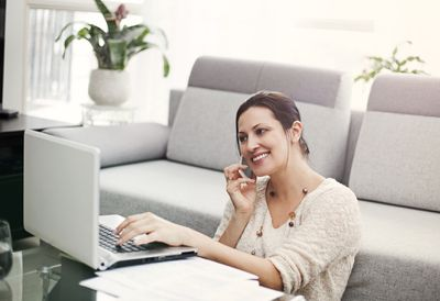 Woman seated on the floor at home working on a laptop