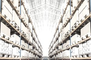 Rows of shelves with boxes in modern warehouse using a warehouse management system.