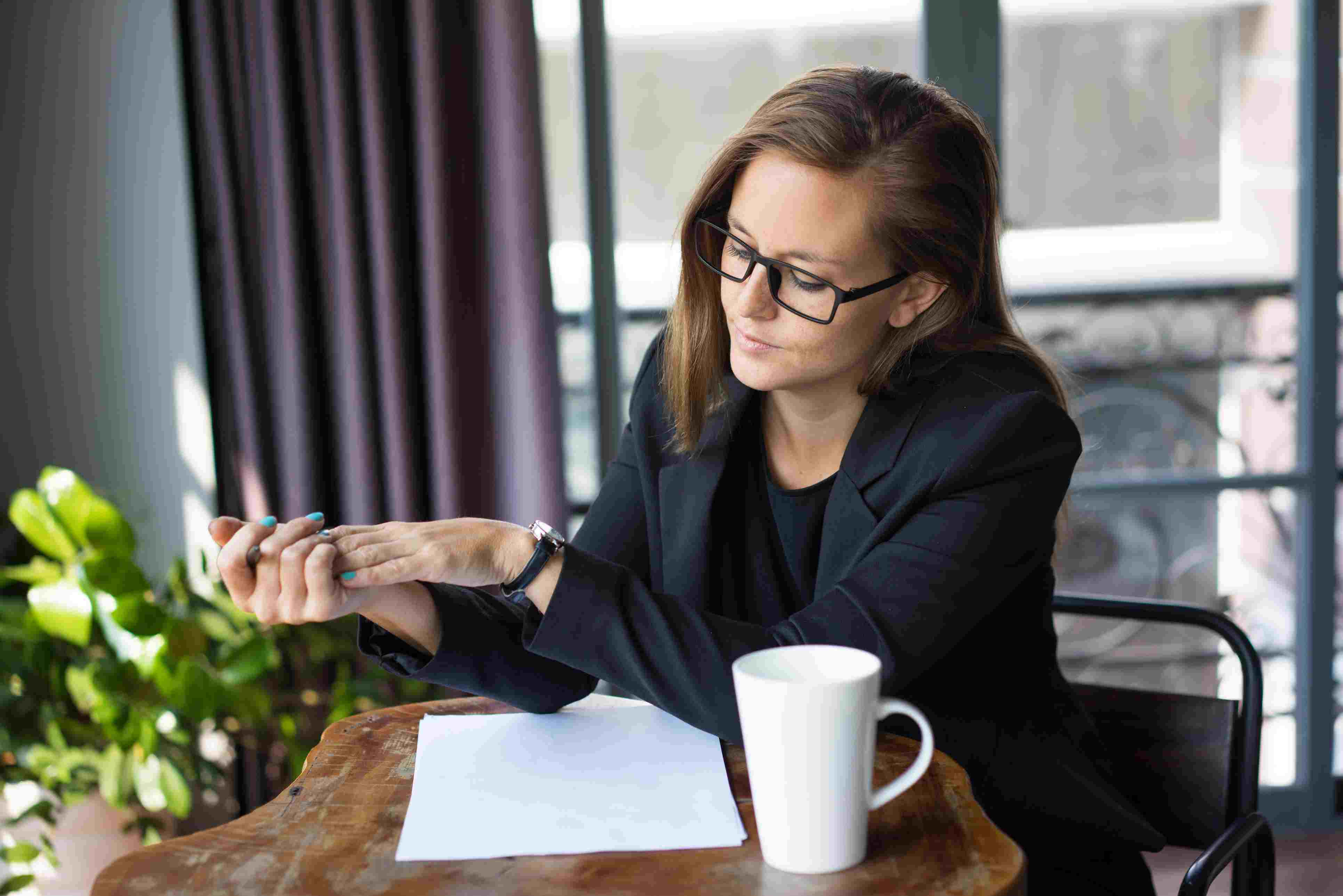 Serious Business Woman Checking Time in Cafe
