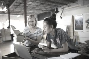 Two young female small business owners researching the impact of small businesses on the economy
