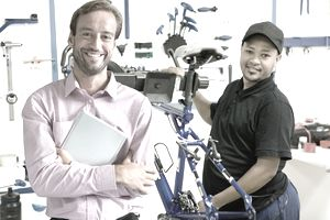 Portrait of store owner and cycle technician in workshop