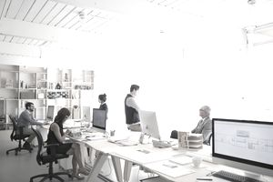 Architects working at computers in open plan office