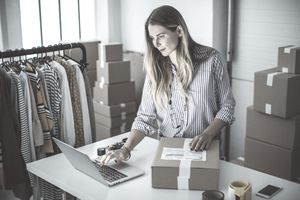A small business owner using a laptop to record shipping products as an expense for tax purposes.