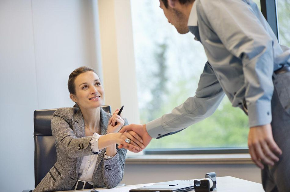 Business executive shaking hands with her client
