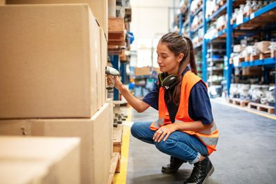 Female worker scanning boxes in warehouse rack