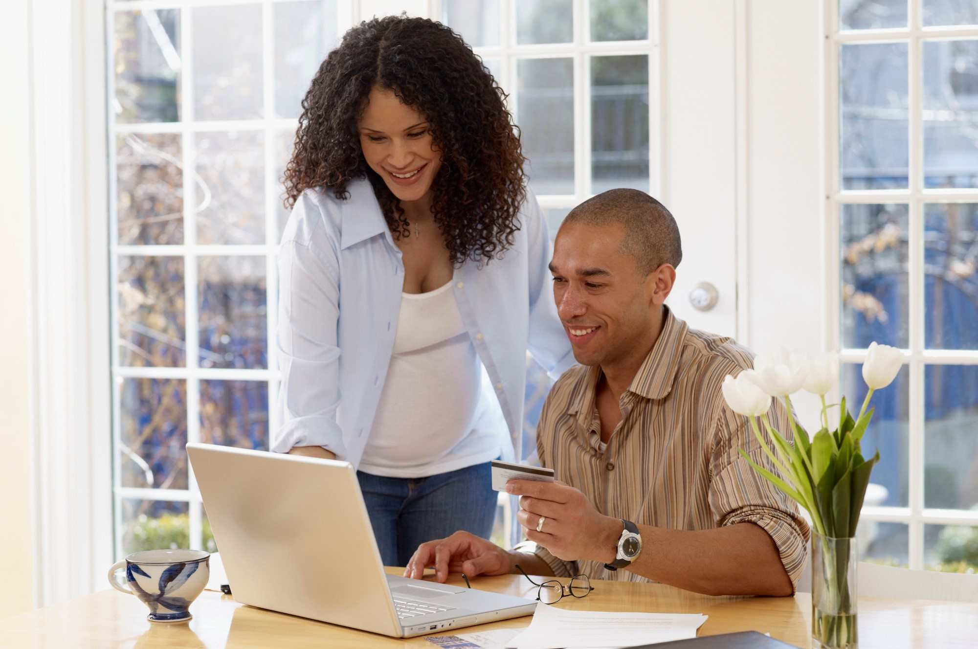 Man holding credit card and looking at laptop with a woman