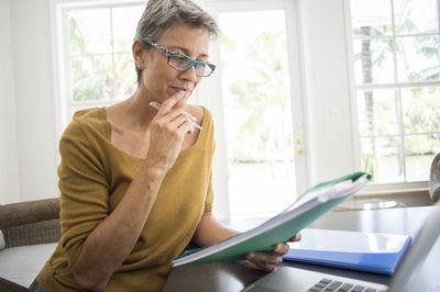 Picture of landlord looking at file at her desk.