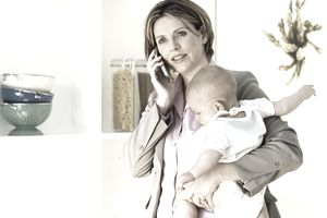 Woman talking on her home business phone while holding a baby.
