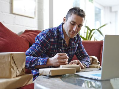 Man in front of laptop with packages surrounding him