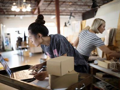 Small business owner doing retail competitor analysis on a laptop in her shop while an employee works in the background.