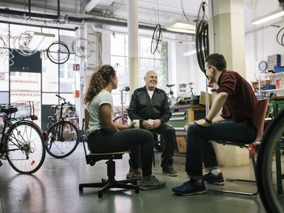 A small team of bicycle mechanics having a meeting together in their bike workshop.