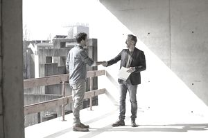 two men, one with contract in hand, shaking hands at construction site