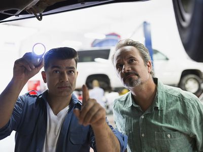 Mechanic and man looking at the underside of car being repaired