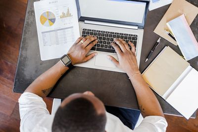 Man using laptop at desk in home office with charts and a budget sheet next to him