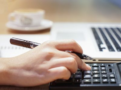 Woman hand working with calculator, business document and laptop computer notebook,