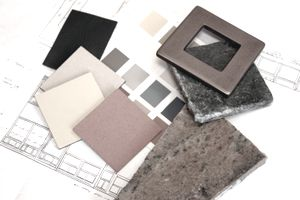 Color samples of paint, stone, granite, stucco and tile sitting on top of blueprints