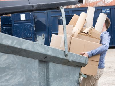 Man carrying an armload of cardboard to the recycling bin.