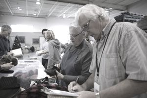 Senior couple with clipboard at clothing drive in warehouse