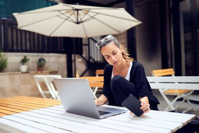 Image shows a woman sitting on a veranda working on her laptop.