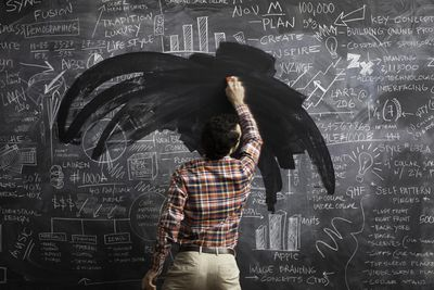 A young male erasing business plans on blackboard