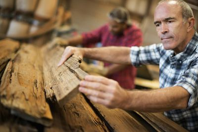 A man measuring and checking planks of wood for re-use and recycling in a reclaimed lumber workshop