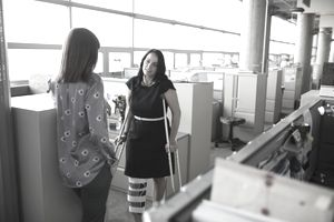 Businesswoman in leg brace on crutches talking to colleague in office