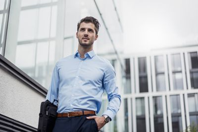 Young business man in light blue oxford shirt and blue pants walking