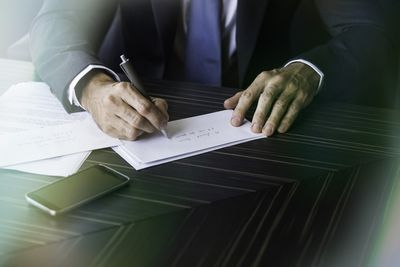Close-up of businessman's hands addressing board invitation letters