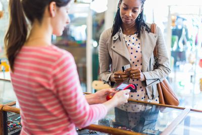 Customer paying for jewelry with contactless payment technology in a retail clothing store