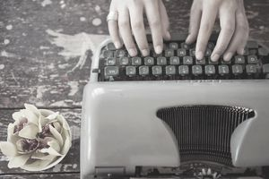 A woman's hands typing on a typewriter