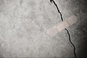 Bandaid over concrete crack, representing concrete crack repairs.
