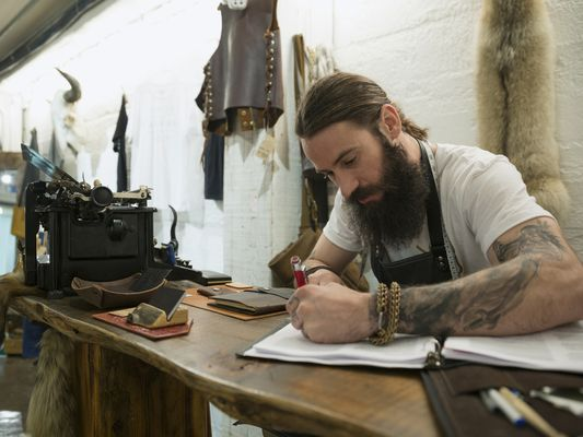 Leather shop owner entrepreneur working on master budget at desk