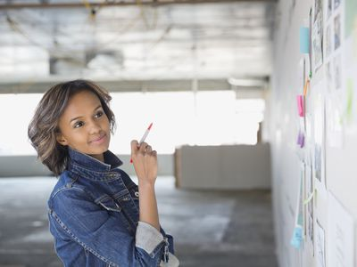 a young woman looking at a whiteboard affixed with post-it notes