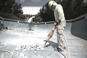 a pair of construction workers using jackhammers to break up concrete in an empty pool