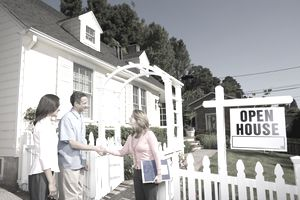 Couple shaking hands with real estate agent at open house