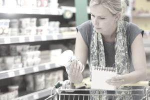 Woman examining a carton of yogurt.