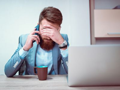 Exhausted business man puts head in his hand while talking on the phone