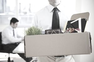 Person walking out of office with box of personal items