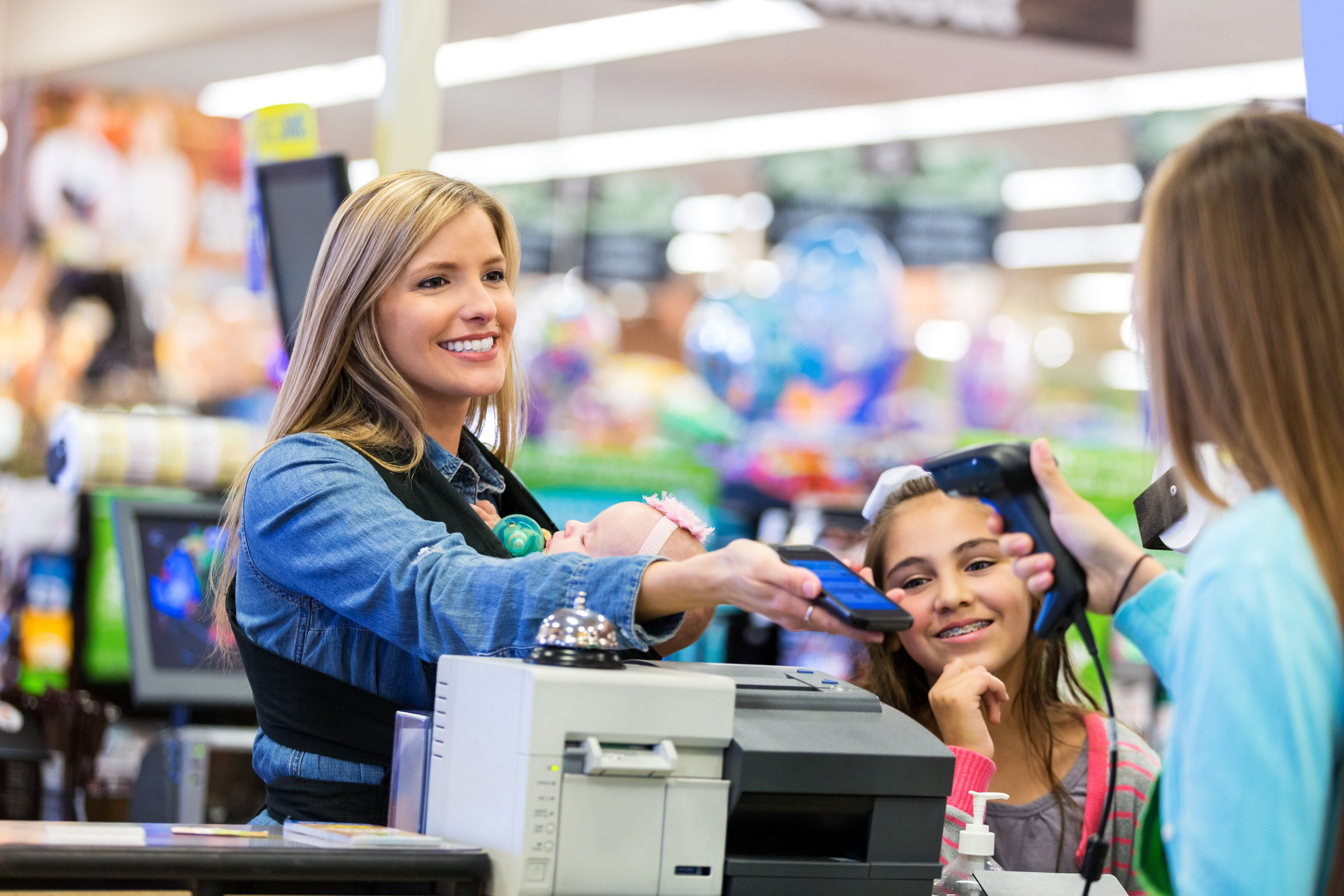 Mother and daughter at checkout using a smart phone to pay for purchases in store.