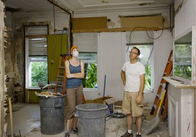 Man and woman standing in room under renovation