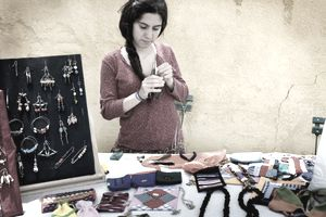 Woman selling jewelery at a craft fair.